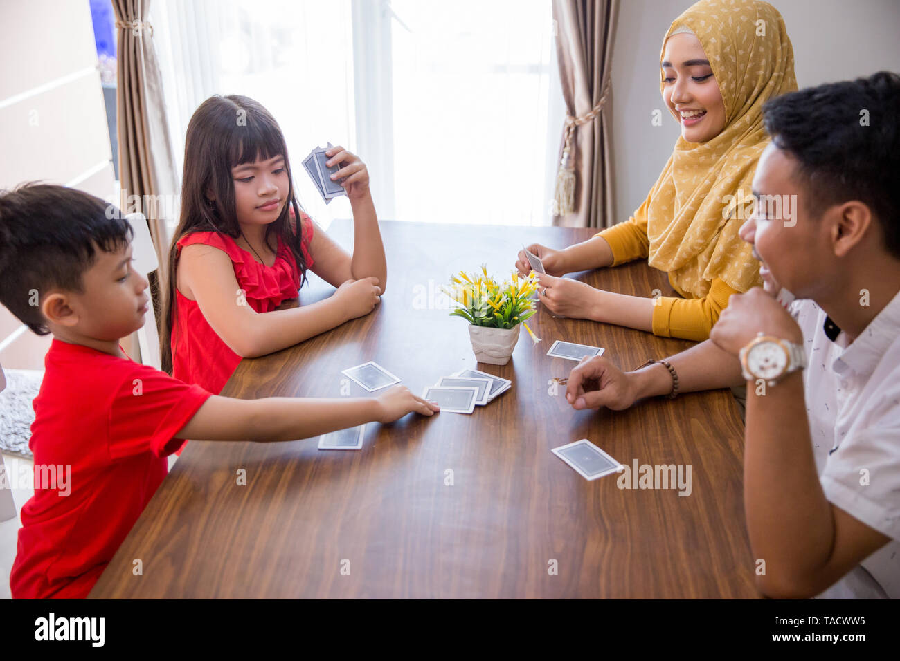 happy asian family playing fun card game together at home - Stock Image