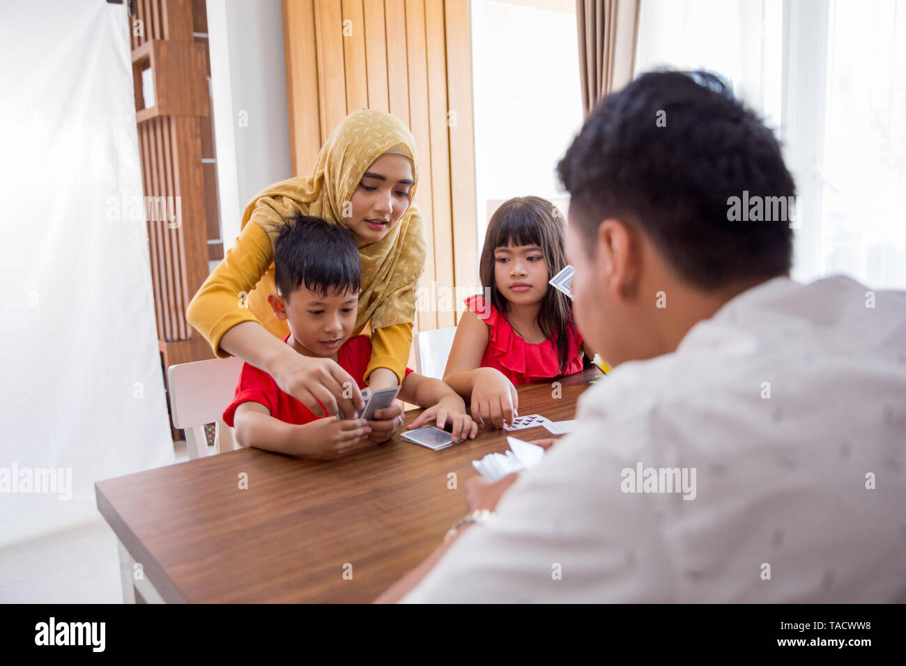 happy asian kids play card game together with parent at home - Stock Image