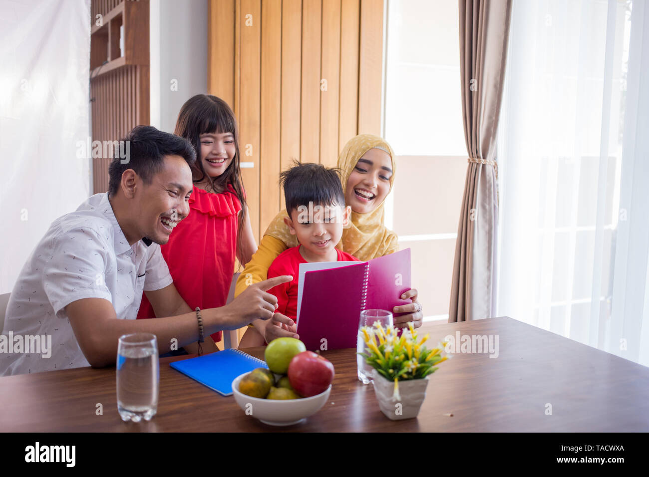 asian family reading a book together at home - Stock Image