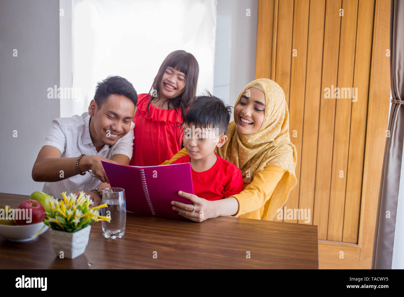 family reading a book together Stock Photo