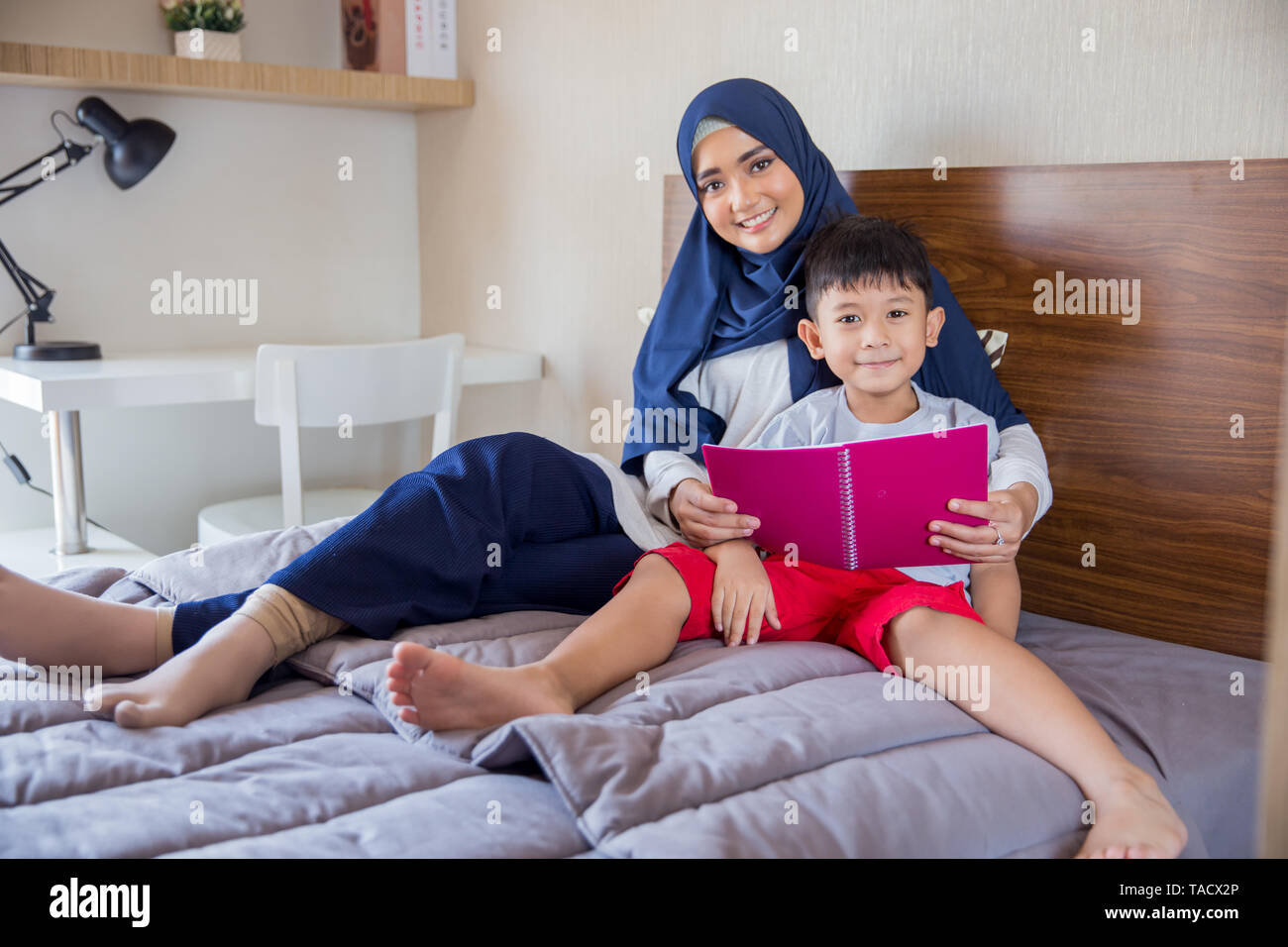 beautiful asian woman with hijab reading book with son - Stock Image