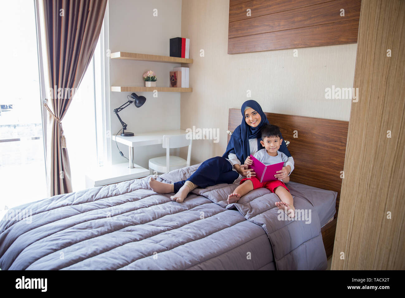 muslim mother reading a book with her boy in bedroom - Stock Image