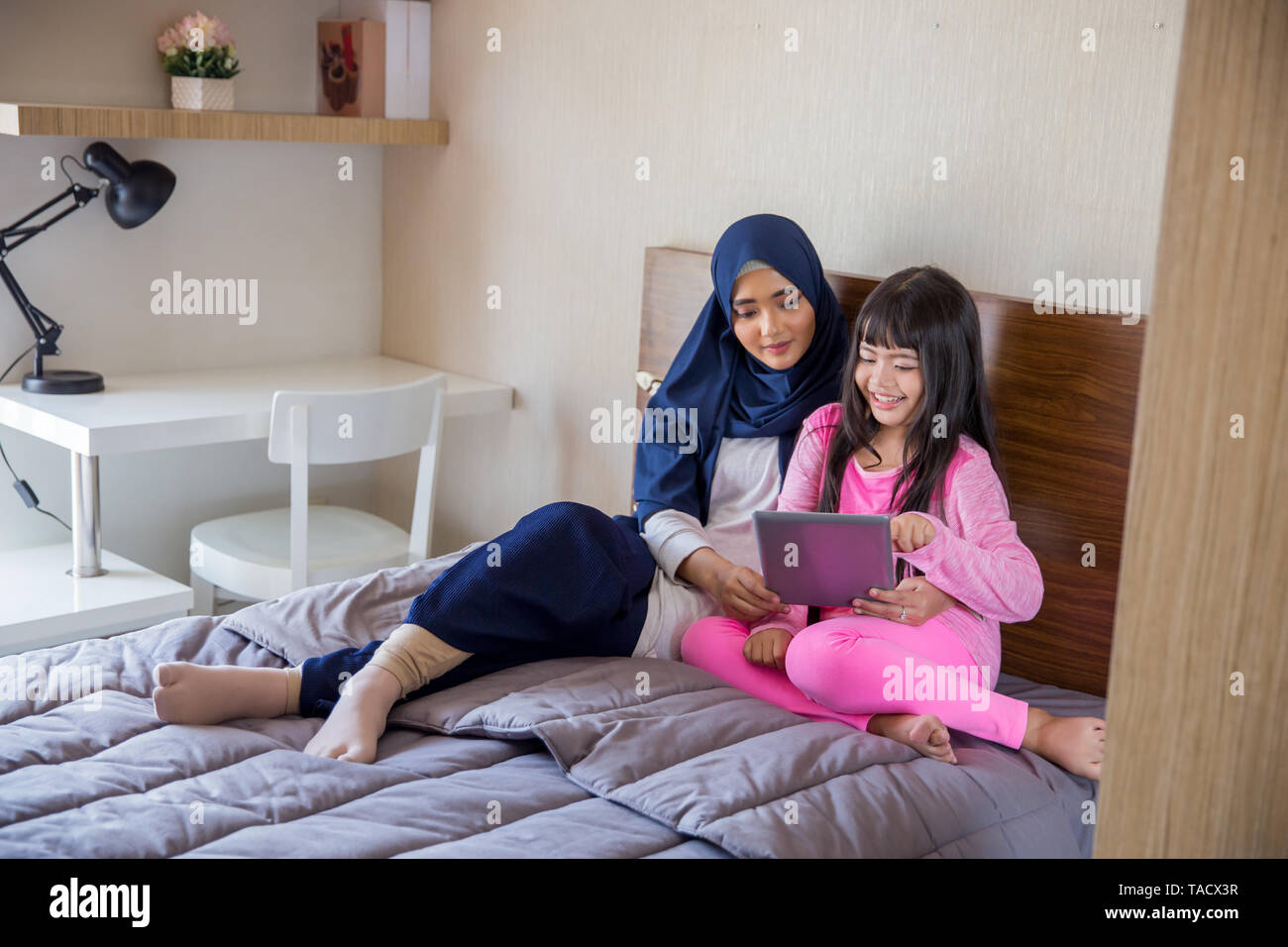 portrait of happy young asian kids with parent using tablet pc - Stock Image