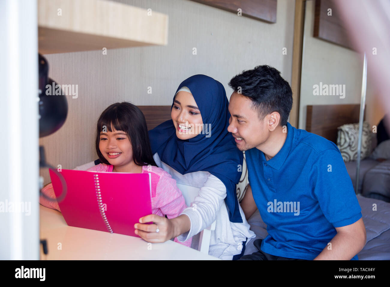 reading a book with family at bedroom together - Stock Image