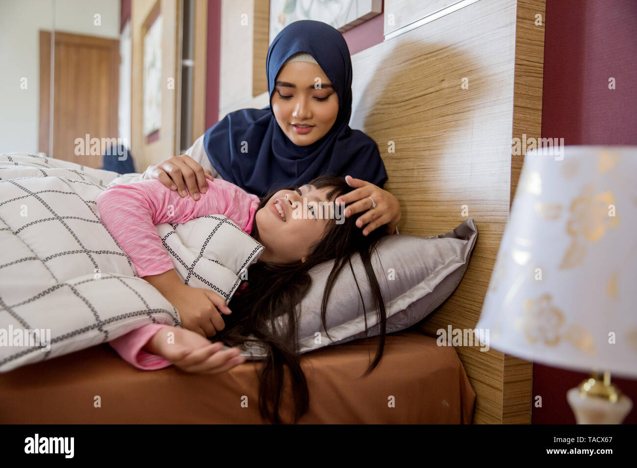 muslim mother in bed with daughter telling story before having a nap - Stock Image