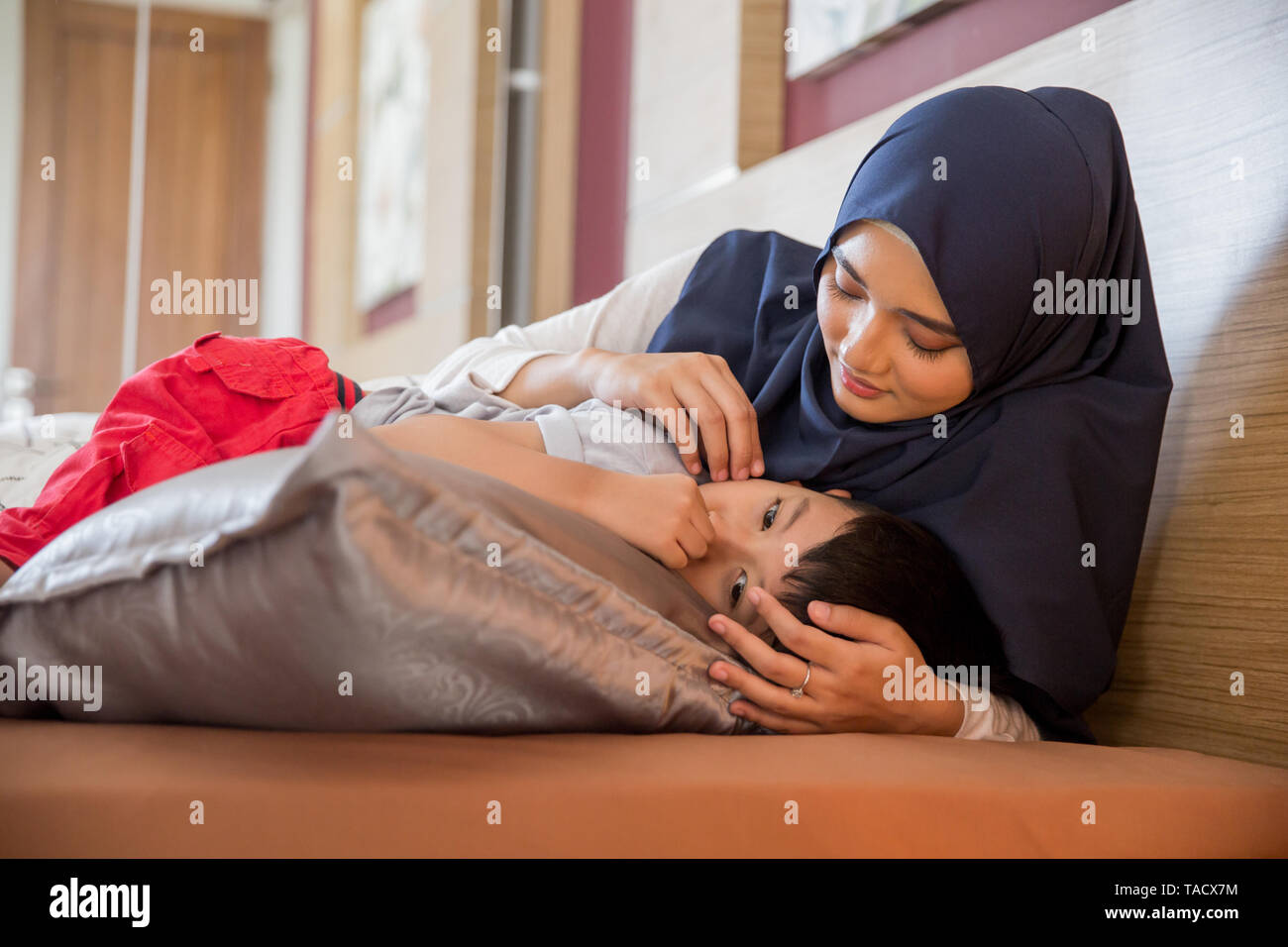 sad boy being comforted by his muslim mother at home - Stock Image