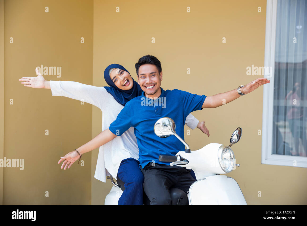 happy asian muslim couple riding motorcyle or scooter - Stock Image