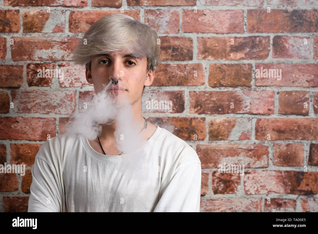 Vaper Smoke outdoor electronic cigarette near the brick wall. Young man smoking big cloud of steam - Stock Image
