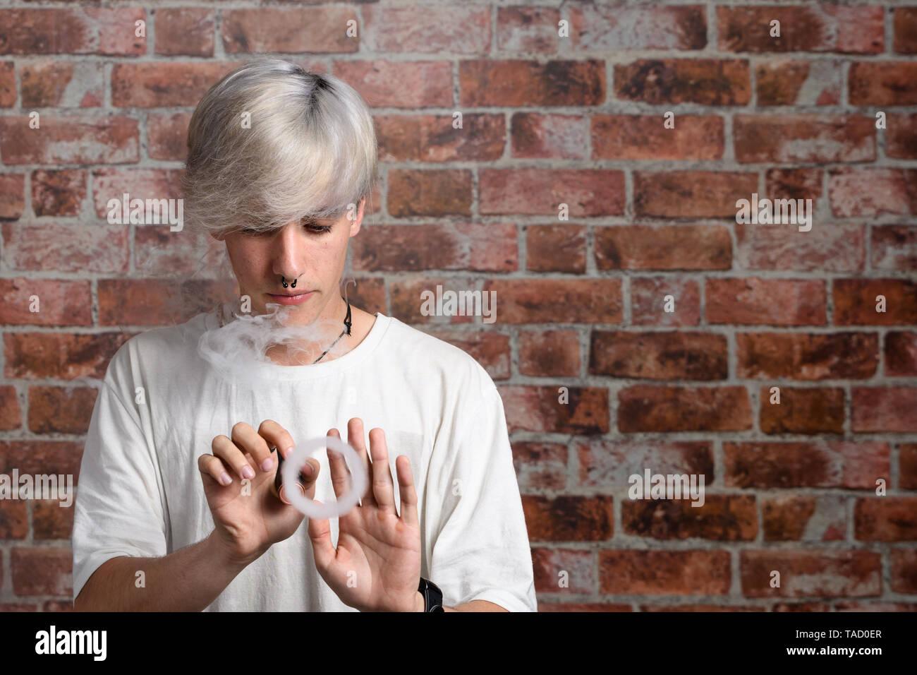 Vaper Smoke outdoor electronic cigarette near the brick wall. Young man smoking big cloud of steam - Stock Image
