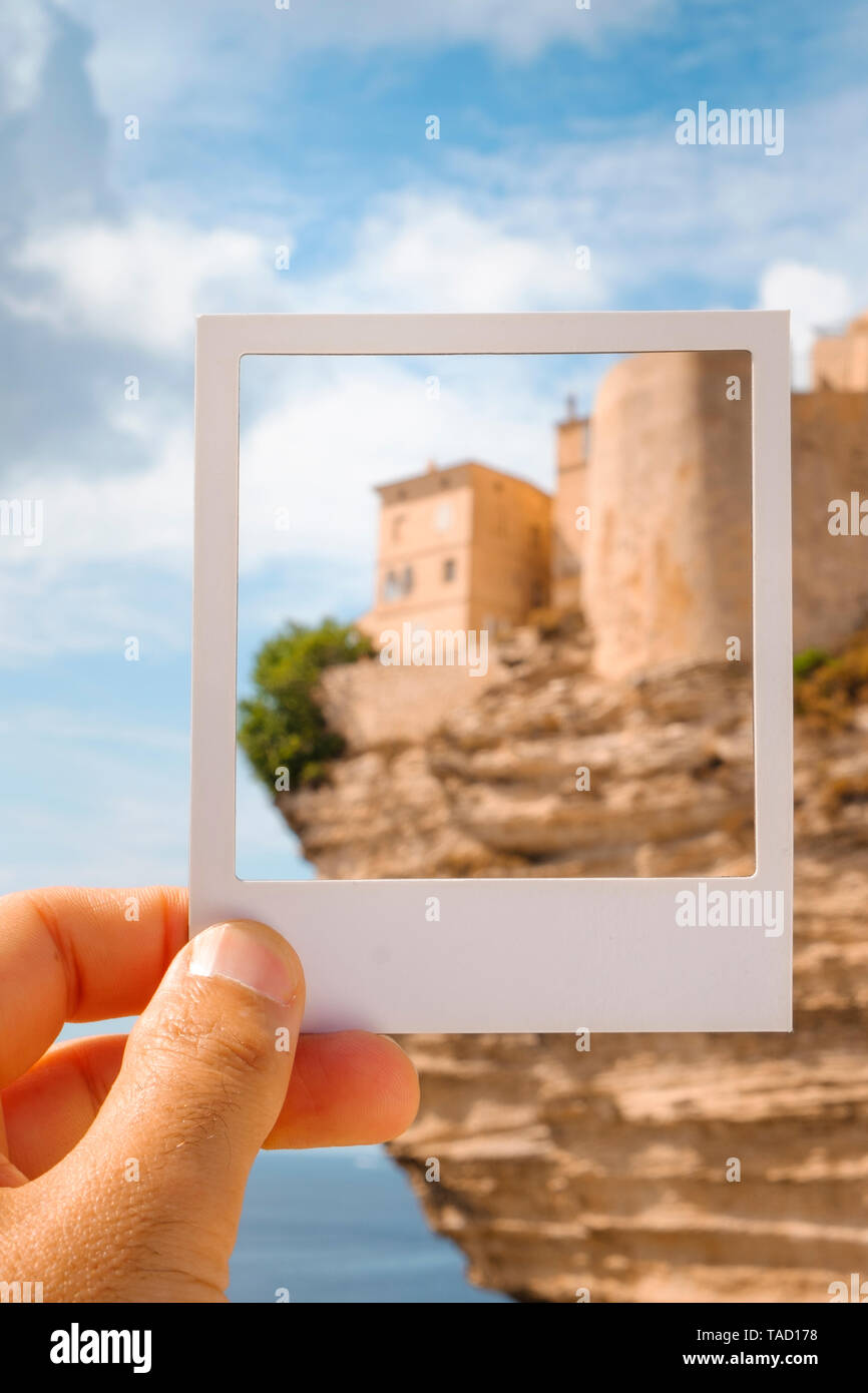 closeup of a young man with a white frame in his hand, framing the Haute Ville, the old town of Bonifacio, in Corsica, France, built on the top of a p - Stock Image