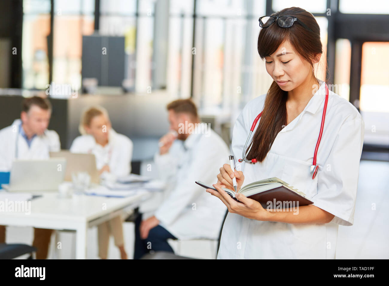 Young female doctor or nurse with calendar while scheduling in hospital - Stock Image