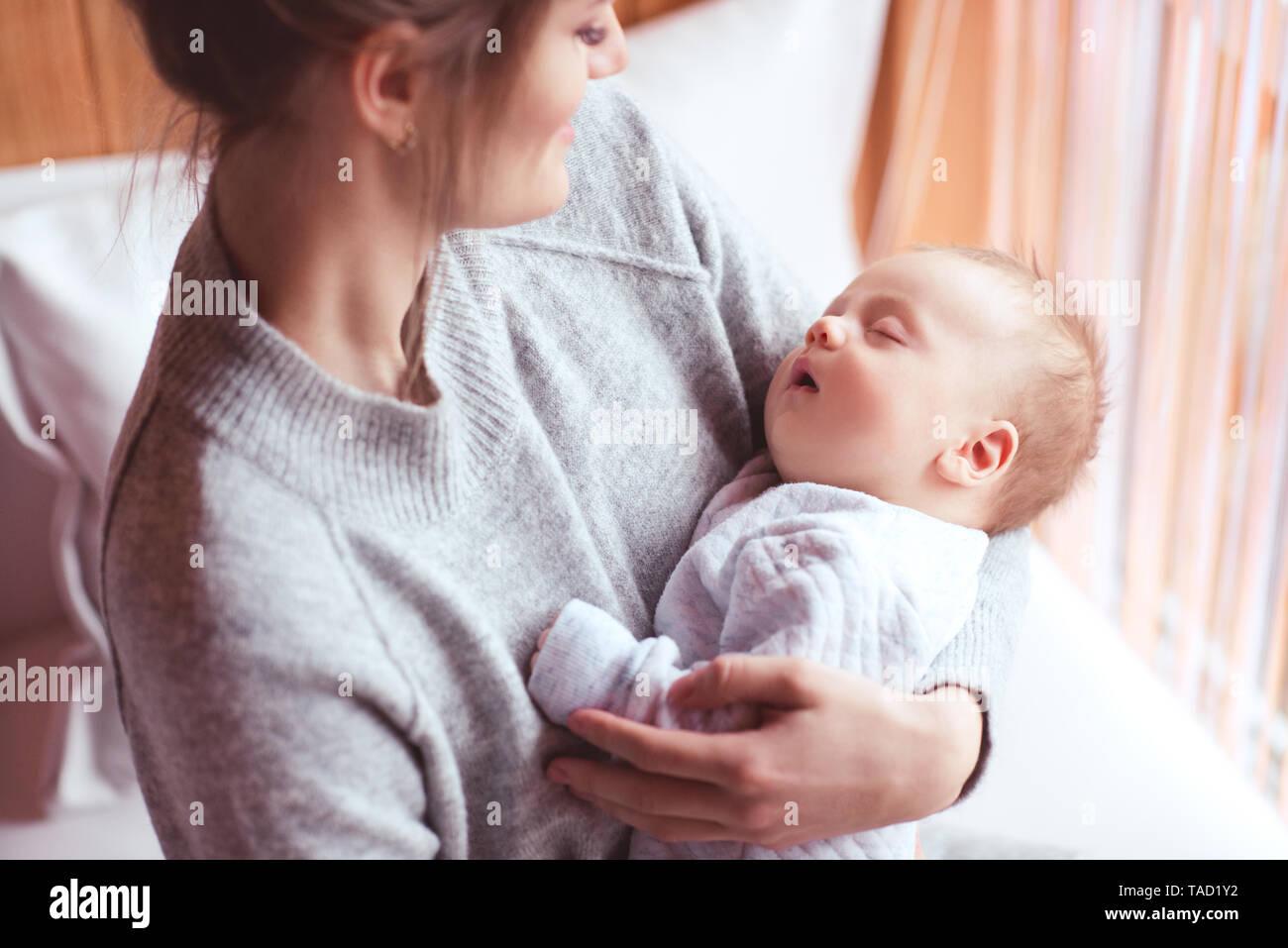 Mother holding sleeping baby boy in room. Motherhood. Maternity. Stock Photo