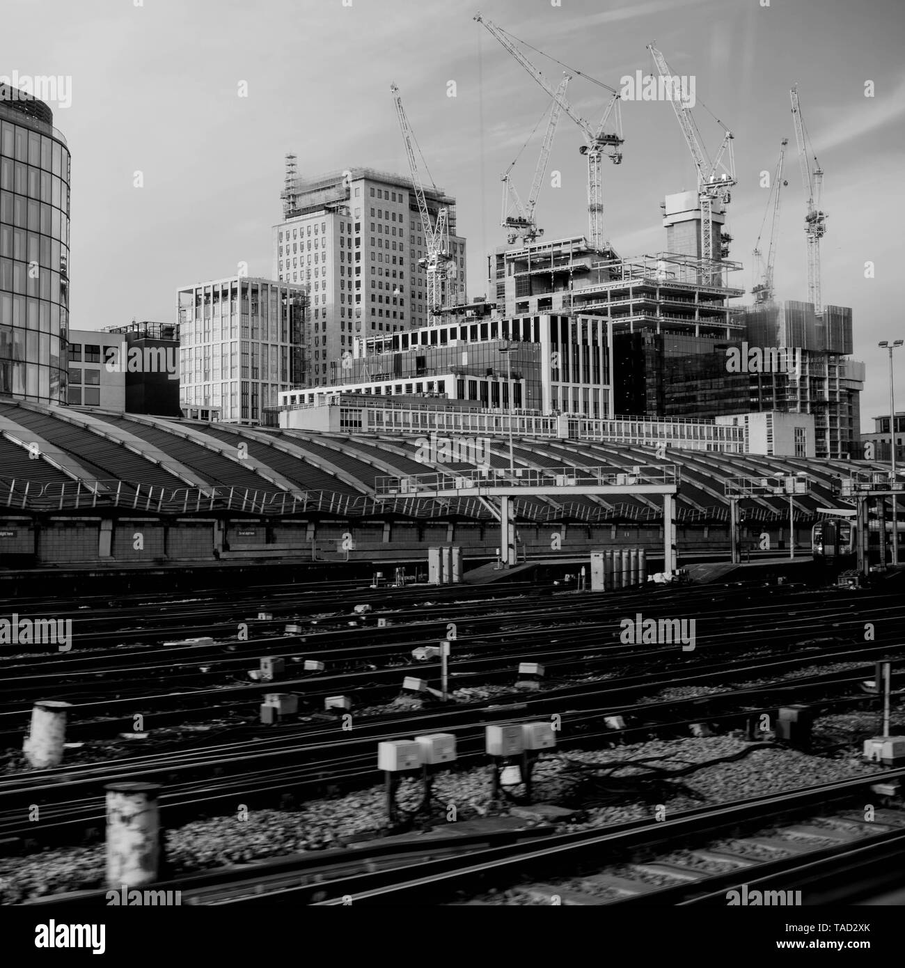 Railway Tracks Leaving Waterloo Station In London With No Trains or People with Tower Cranes and Construction Work in the Background - Stock Image