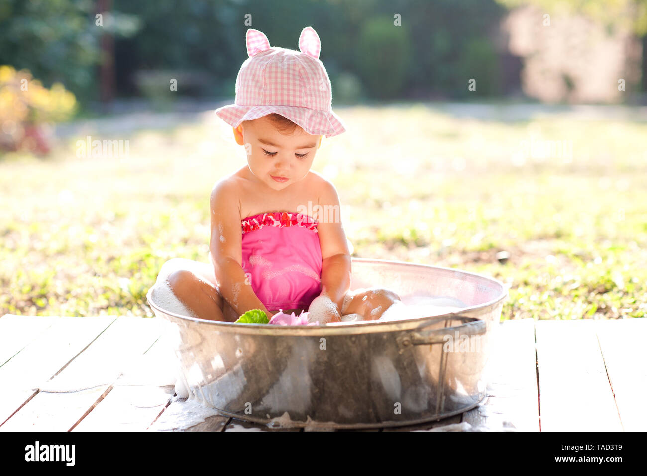 Cute baby girl taking bath outdoors. Playing in bathtub with soap foam. Stock Photo