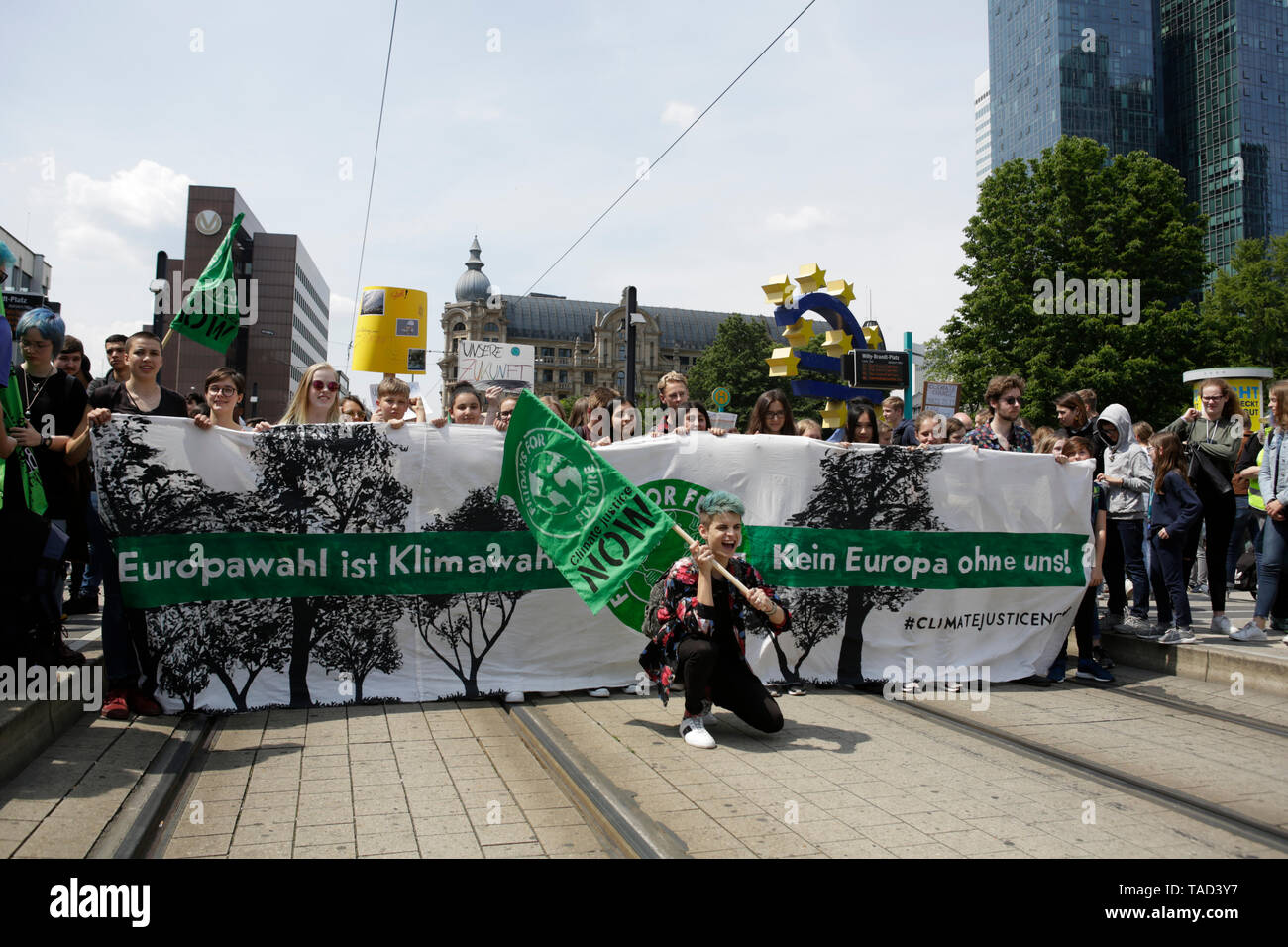 Frankfurt, Germany. 24th May 2019. The people at the banner at the front of the march pose for a picture. The large Euro sign can be seen in the background. Around 4,500 young people marched through Frankfurt to the European Central Bank, to protest against the climate change and for the introduction of measurements against it. The protest took place as part of an Europe wide climate strike, two days ahead of the 2019 European elections. - Stock Image
