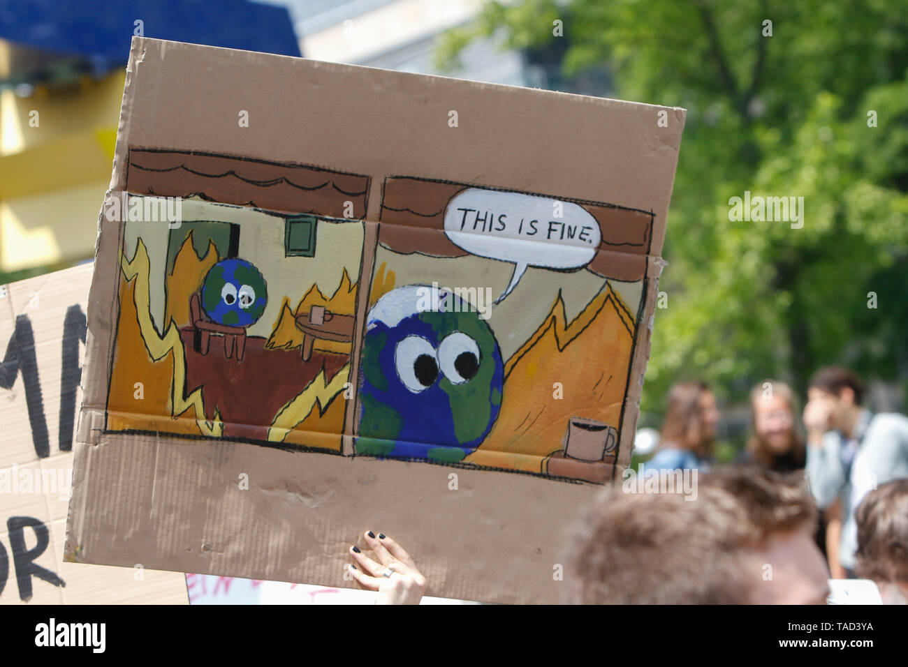 Frankfurt, Germany. 24th May 2019. A protester carries a sign with a cartoon of the planet Earth in a burning room that reads 'This is fine'. Around 4,500 young people marched through Frankfurt to the European Central Bank, to protest against the climate change and for the introduction of measurements against it. The protest took place as part of an Europe wide climate strike, two days ahead of the 2019 European elections. - Stock Image