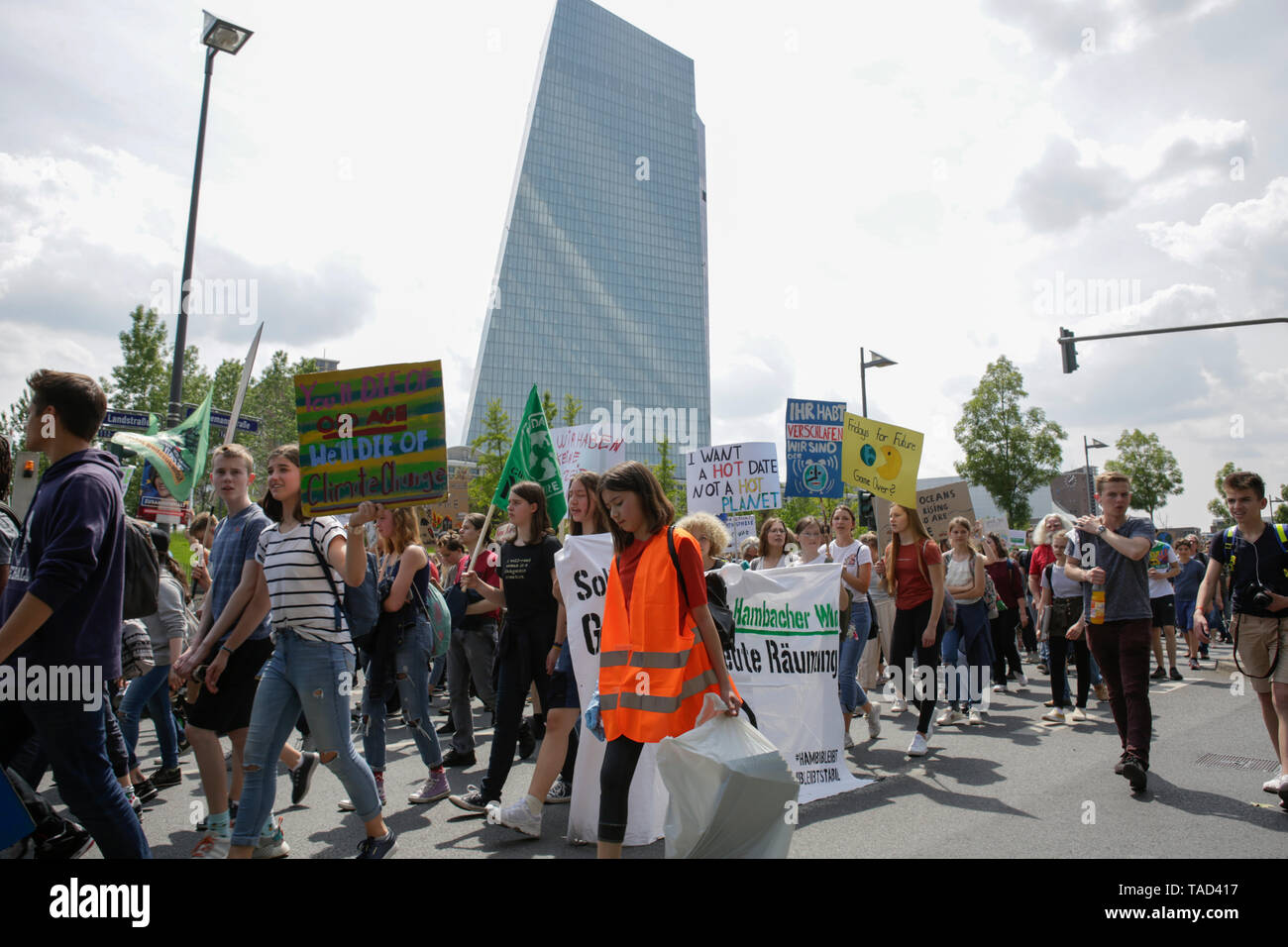Frankfurt, Germany. 24th May 2019. The protesters march with self-made signs past the ECB (European Central Bank) building. Around 4,500 young people marched through Frankfurt to the European Central Bank, to protest against the climate change and for the introduction of measurements against it. The protest took place as part of an Europe wide climate strike, two days ahead of the 2019 European elections. - Stock Image