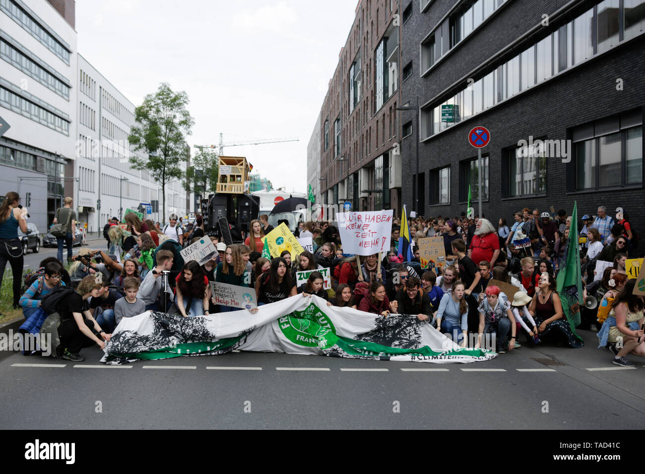 Frankfurt, Germany. 24th May 2019. The protesters stage a short sit-in protest. Around 4,500 young people marched through Frankfurt to the European Central Bank, to protest against the climate change and for the introduction of measurements against it. The protest took place as part of an Europe wide climate strike, two days ahead of the 2019 European elections. - Stock Image