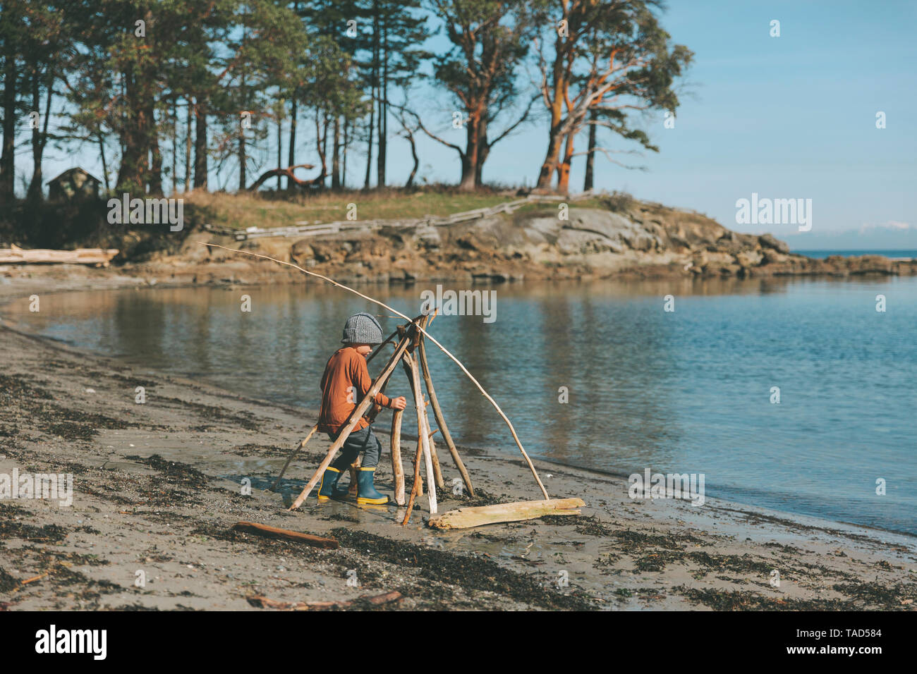 Boy playing on a the beach, building a drift wood fort - Stock Image