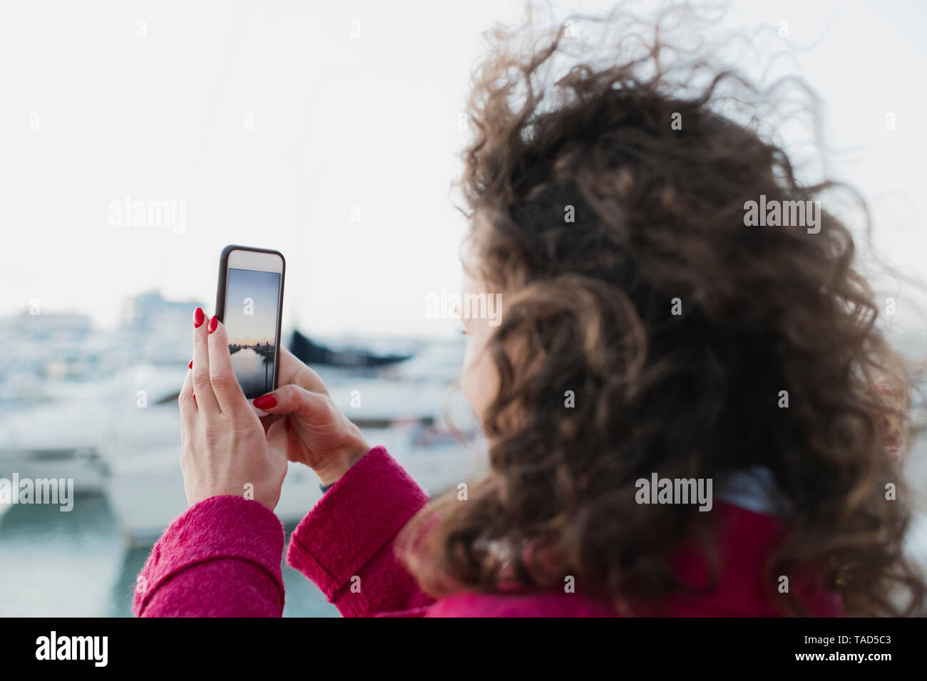 Woman with curly hair taking a cell phone picture - Stock Image