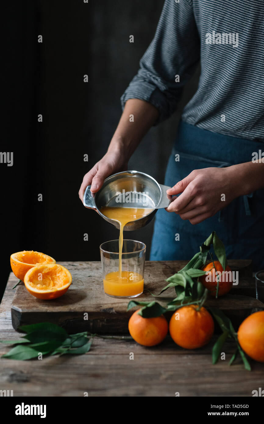Young man pouring freshly squeezed orange juice into a glass, partial view - Stock Image