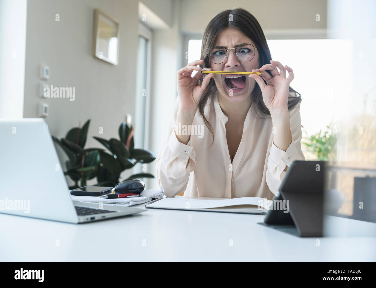 Young woman sitting at table at home grimacing - Stock Image
