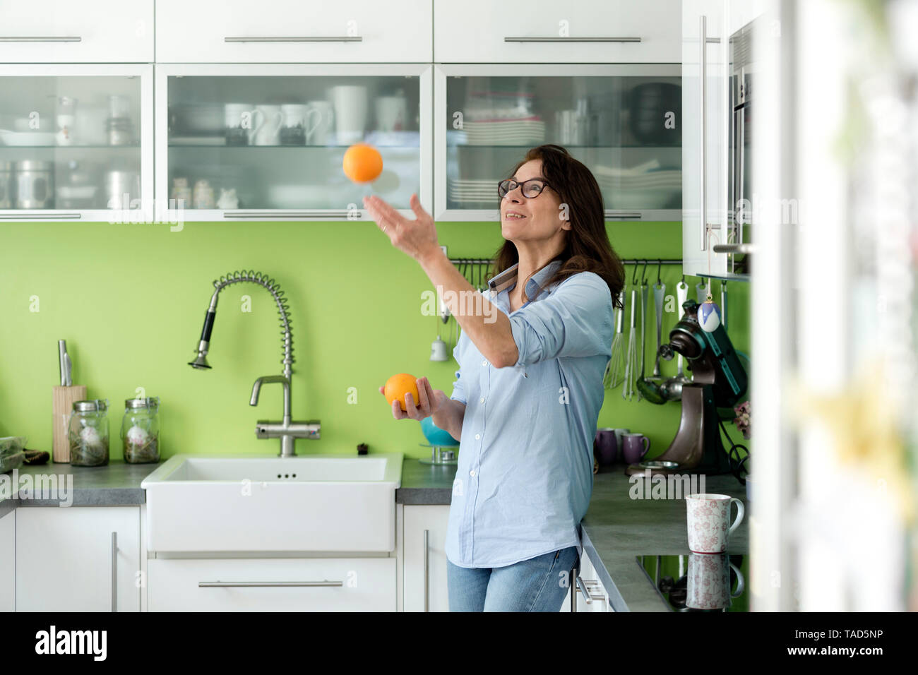 Mature woman juggling with oranges in kitchen at home - Stock Image