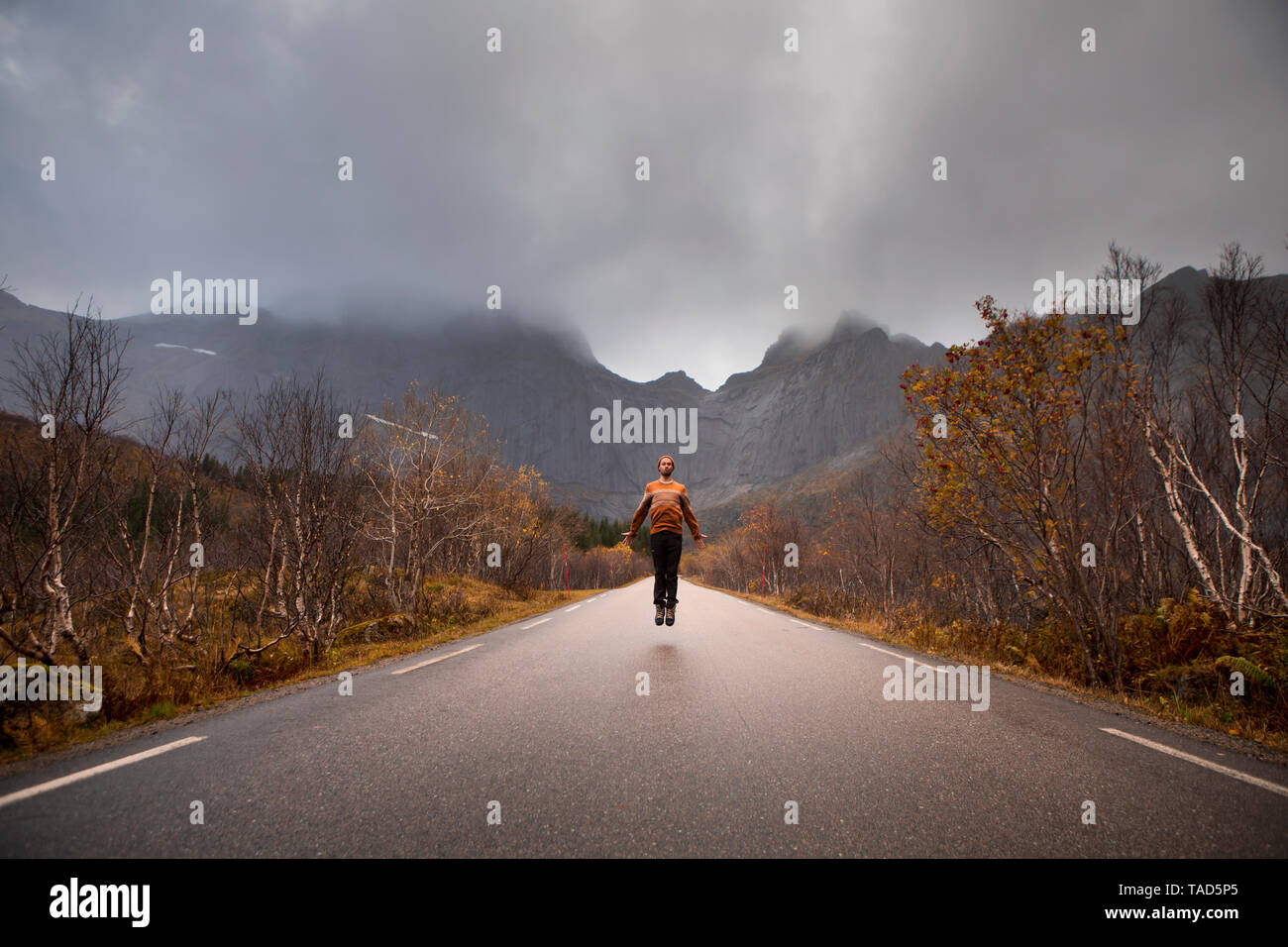 Norway, Lofoten Islands, man jumping on empty road surrounded by rock face - Stock Image