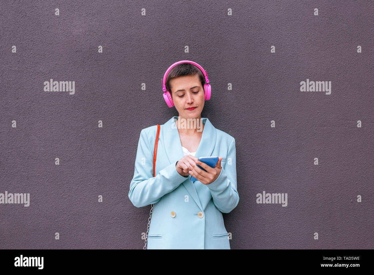 Woman dressed in jacket listening to music with her mobile phone - Stock Image