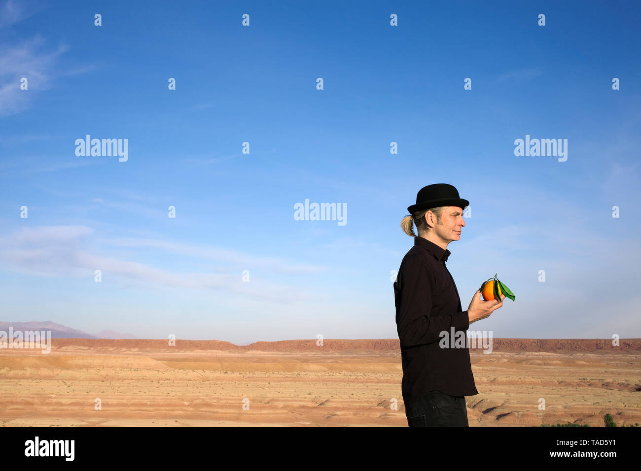 Morocco, Ounila Valley, man wearing a bowler hat holding an orange - Stock Image