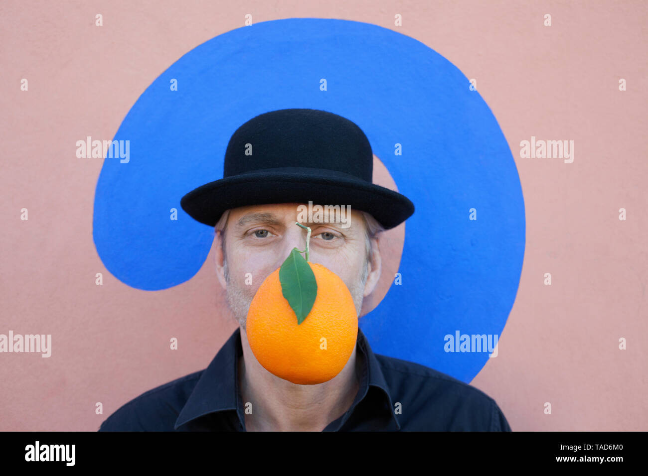 Portrait of man with an orange at a wall with question mark wearing a bowler hat - Stock Image