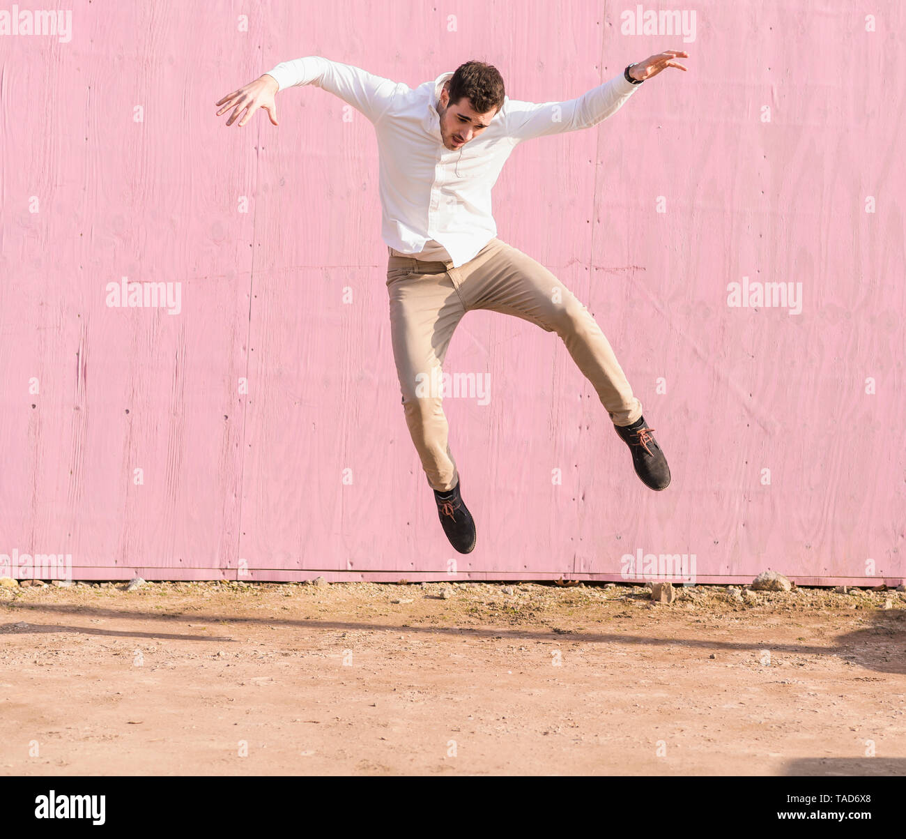 Exuberant young man jumping in front of pink wall - Stock Image