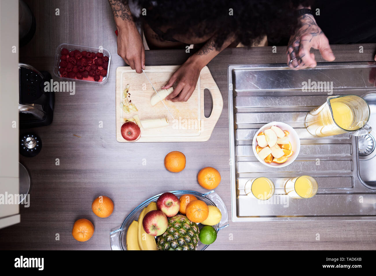 Top view of couple cutting fruit in kitchen - Stock Image