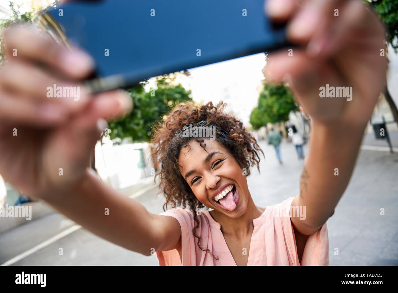 Carefree young woman taking a selfie in the city - Stock Image
