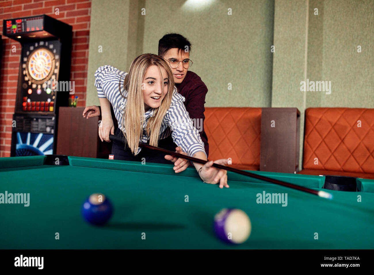 Young man guiding girlfriend at billiard table - Stock Image