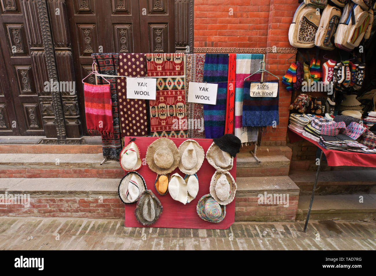 Handicrafts and souvenirs are for sale in a narrow alley off Durbar Square, Bhaktapur, Kathmandu Valley, Nepal - Stock Image