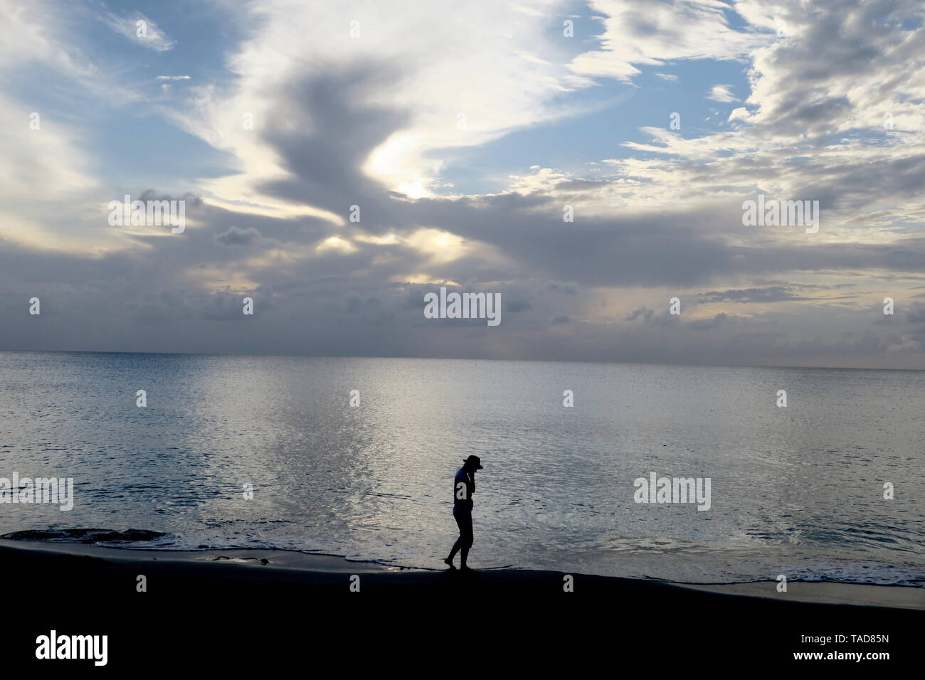 Single person walking on the beach at sunset - Stock Image