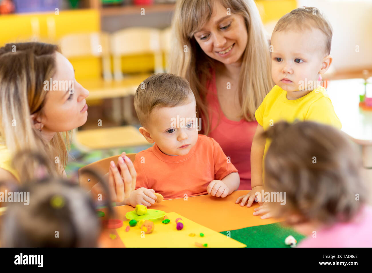 Babies with teacher play colorful clay toy in nursery - Stock Image