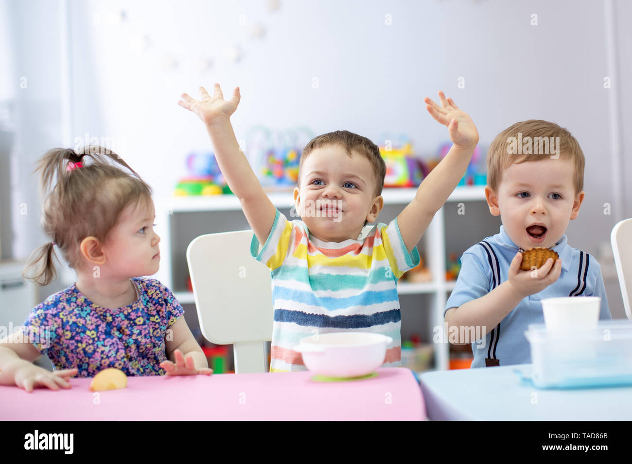 Group of happy children one year old have a lunch in kindergarten - Stock Image