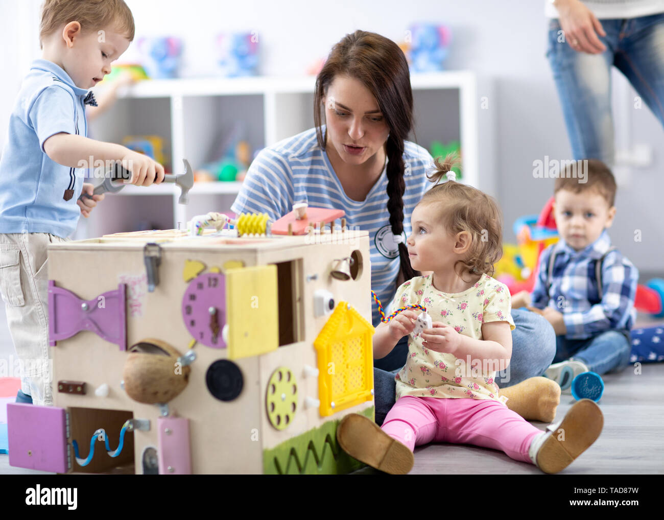 Babies playing with educational toys in nursery - Stock Image