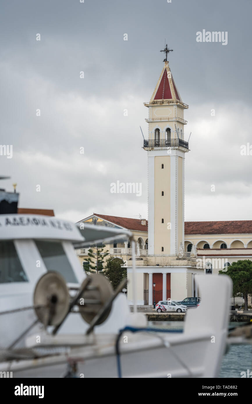 Zakynthos, Greece -  April 2019 : Boat in front of the Saint Dionysios bell tower of the Agios Dionisios church, Zante Island, Zakynthos Town - Stock Image