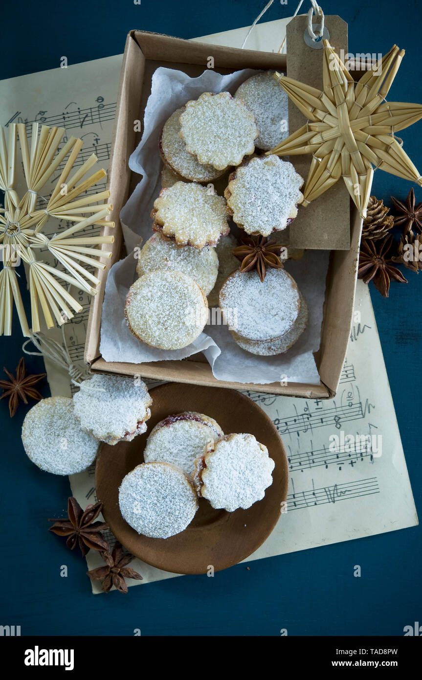 Christmas Cookies Spitzbuben in a box, music sheet, straw stars, star anise, larch cones, gift tag Stock Photo