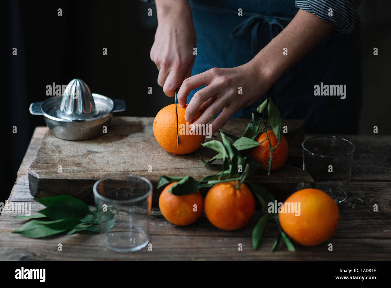 Young man's hands cutting oranges - Stock Image