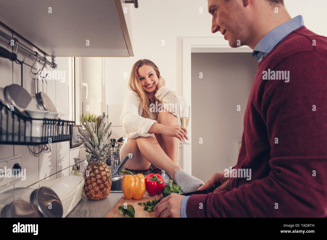 Young couple in kitchen cooking and drinking champagne - Stock Image
