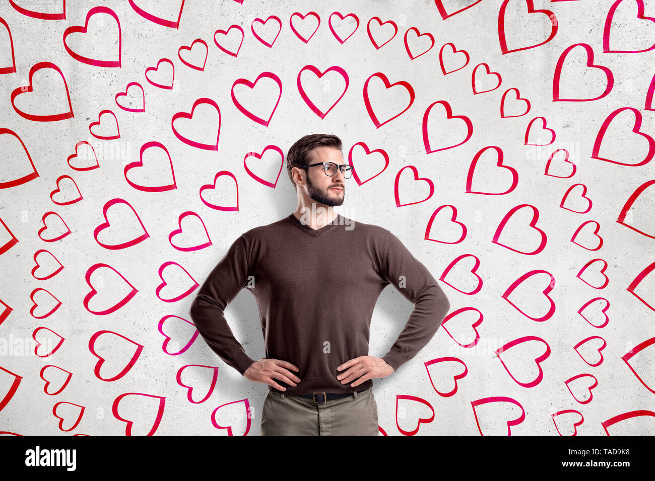 Handsome young man wearing glasses, standing with hands on waist, looking away, at wall with circular pattern of many hand-drawn hearts. St. Valentine - Stock Image