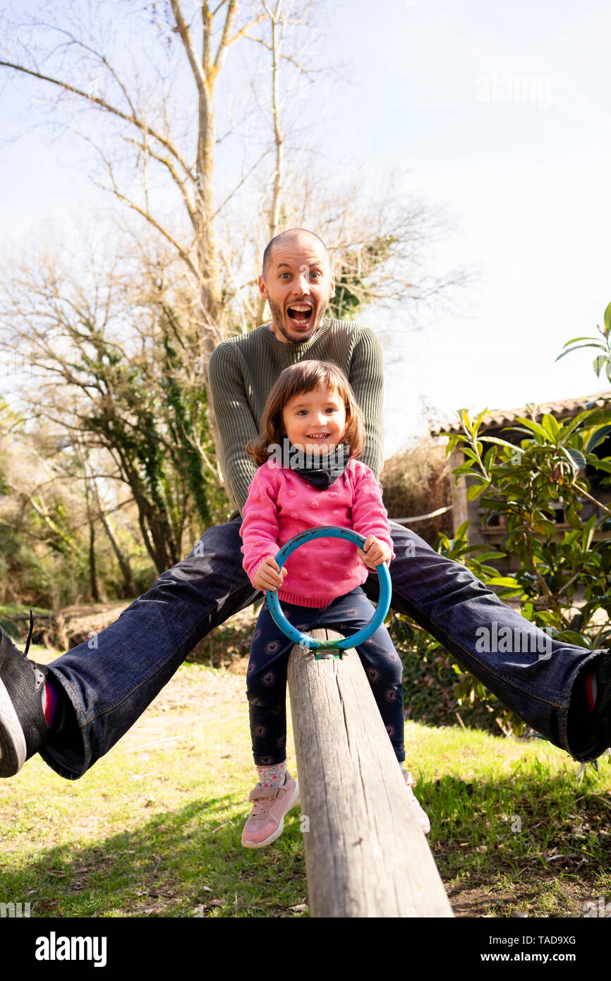 Portrait of father and little daughter having fun together on seesaw - Stock Image