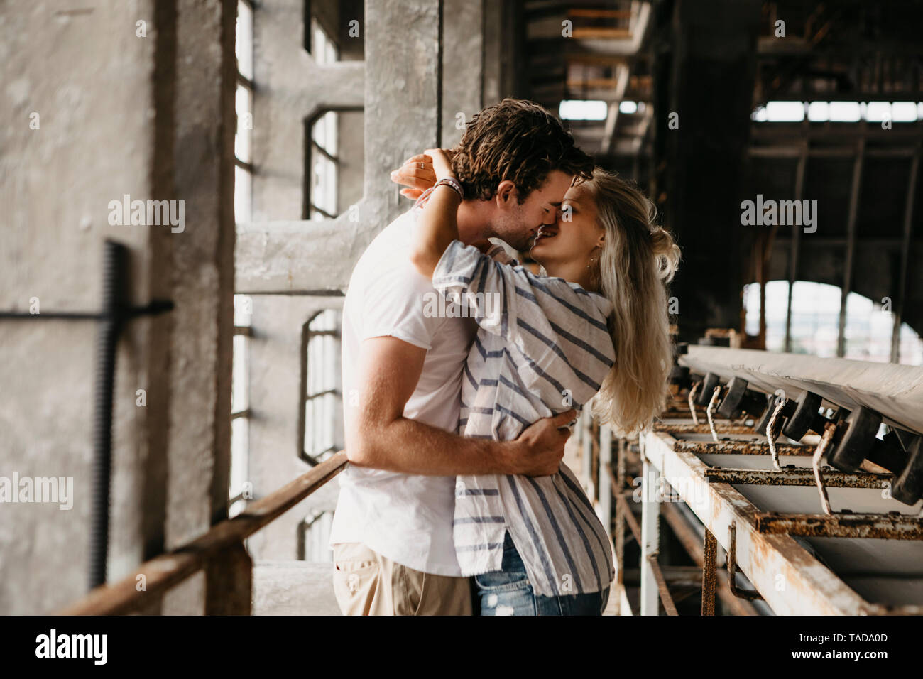 Young couple kissing in an old train station - Stock Image
