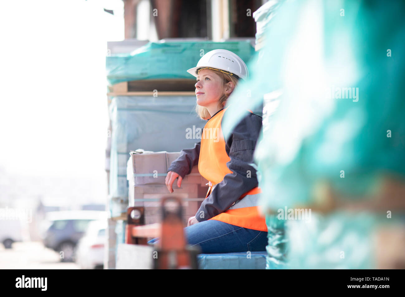 Woman wearing reflective vest and hard hat sitting on building material Stock Photo
