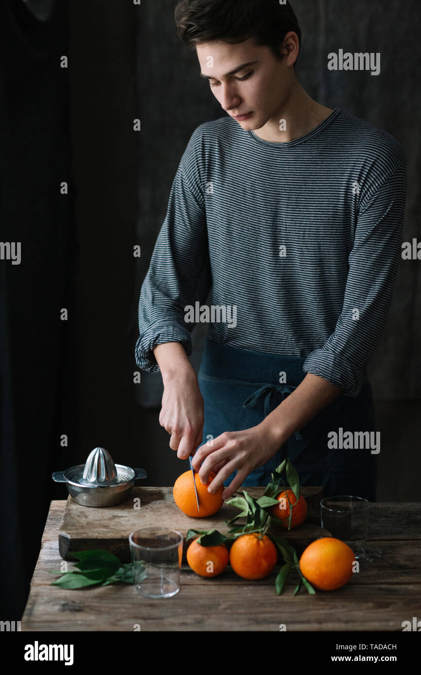 Young man cutting oranges - Stock Image