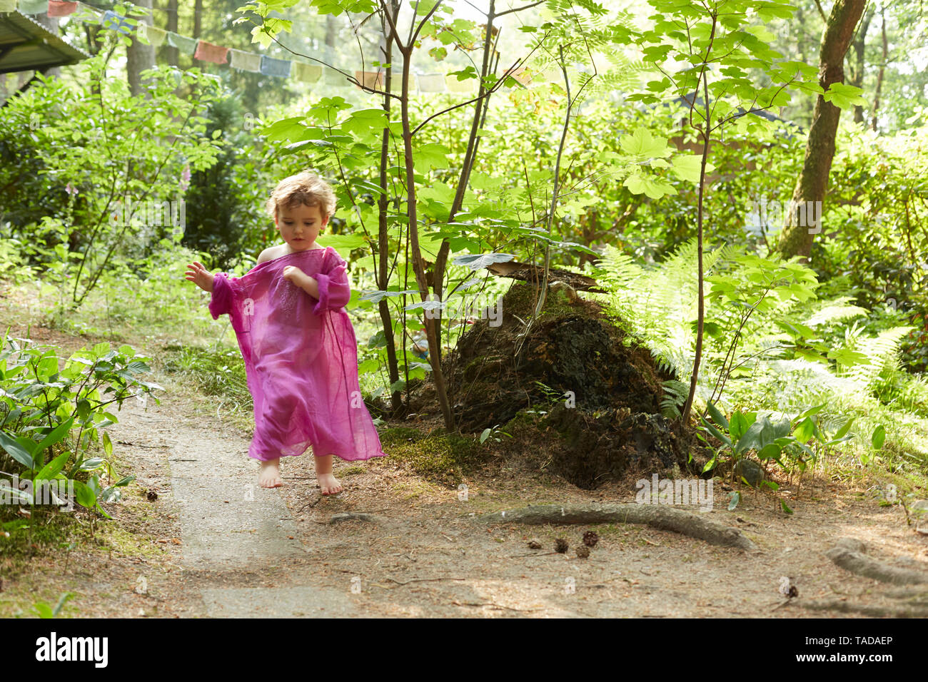 Little girl wearing pink tunic running in nature - Stock Image